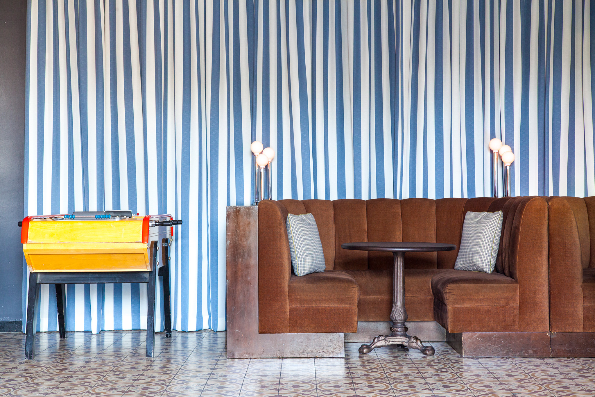 Yellow foosball table and brown plush booth seating against blue and white striped floor to ceiling drapery. Decorative tile flooring.