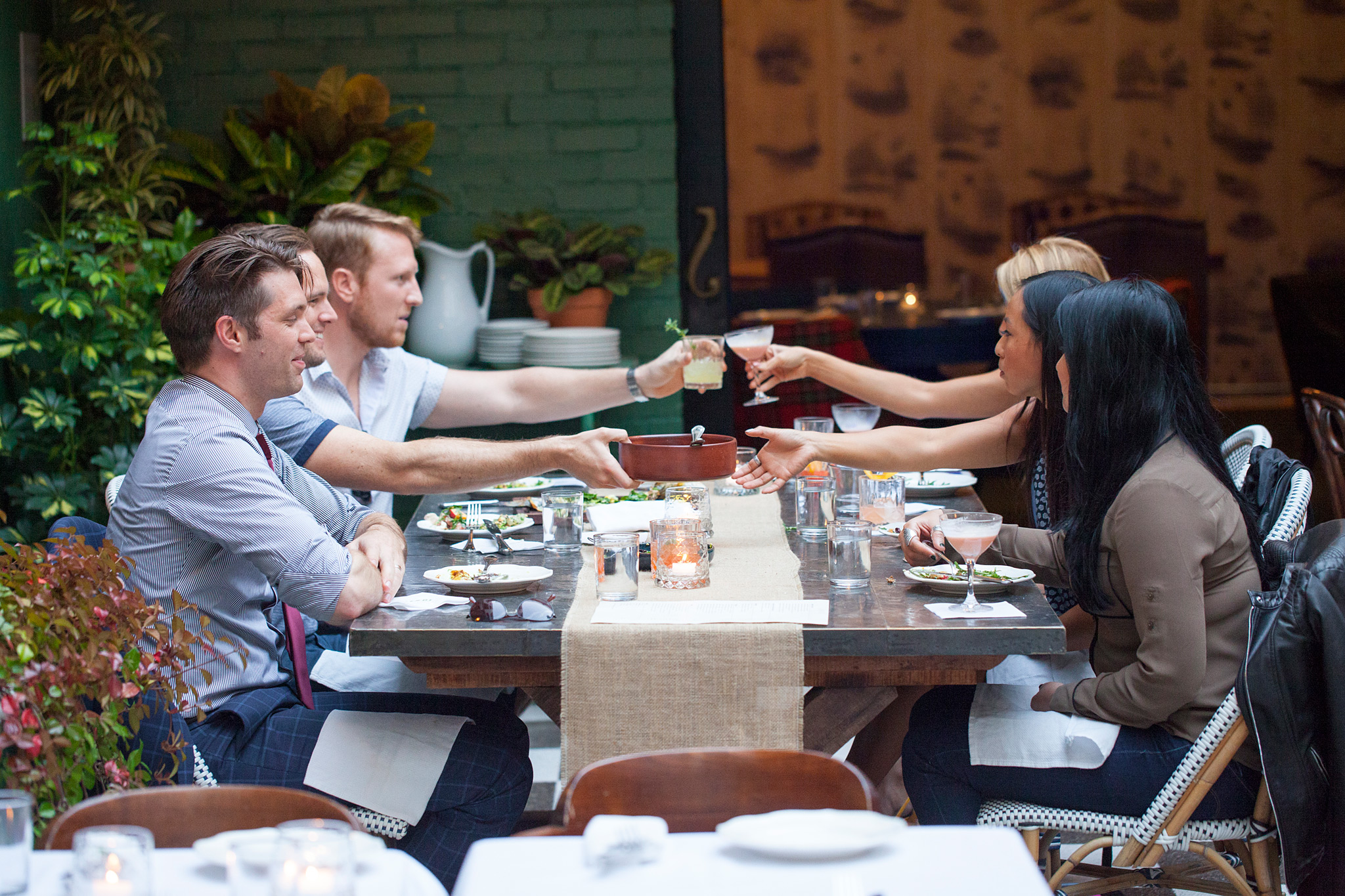 group of happy 20-somethings dining and toasting each other at large metal toppped table in courtyard surrounded by other tables and lush green plants
