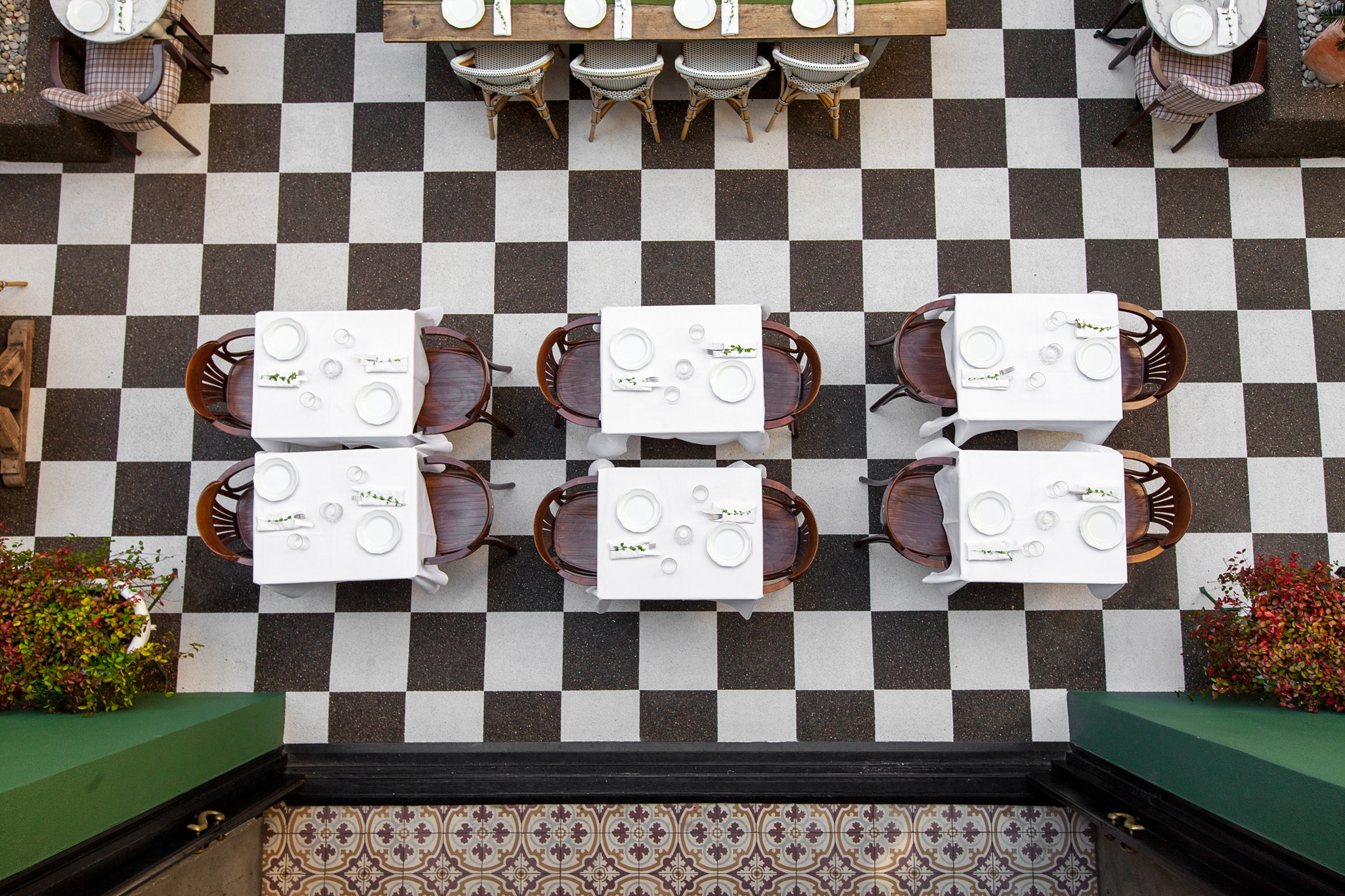 birds-eye view of courtyard, checker patterned floor, white marble and reclaimed wood tables with wood chairs tastefully set for service