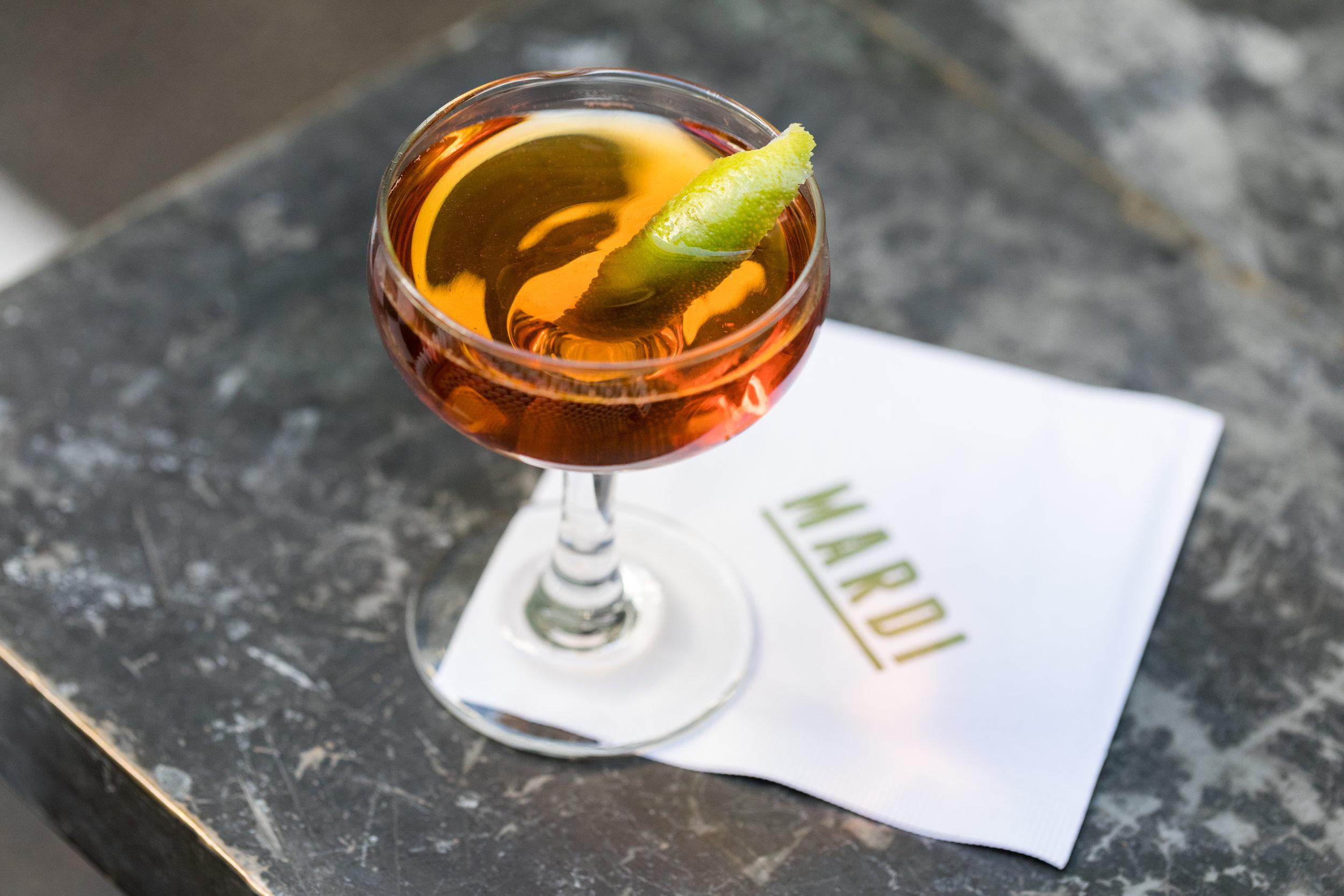 Orange cocktail with lime garnish on Mardi branded napkin, all on corner of grey metal table.