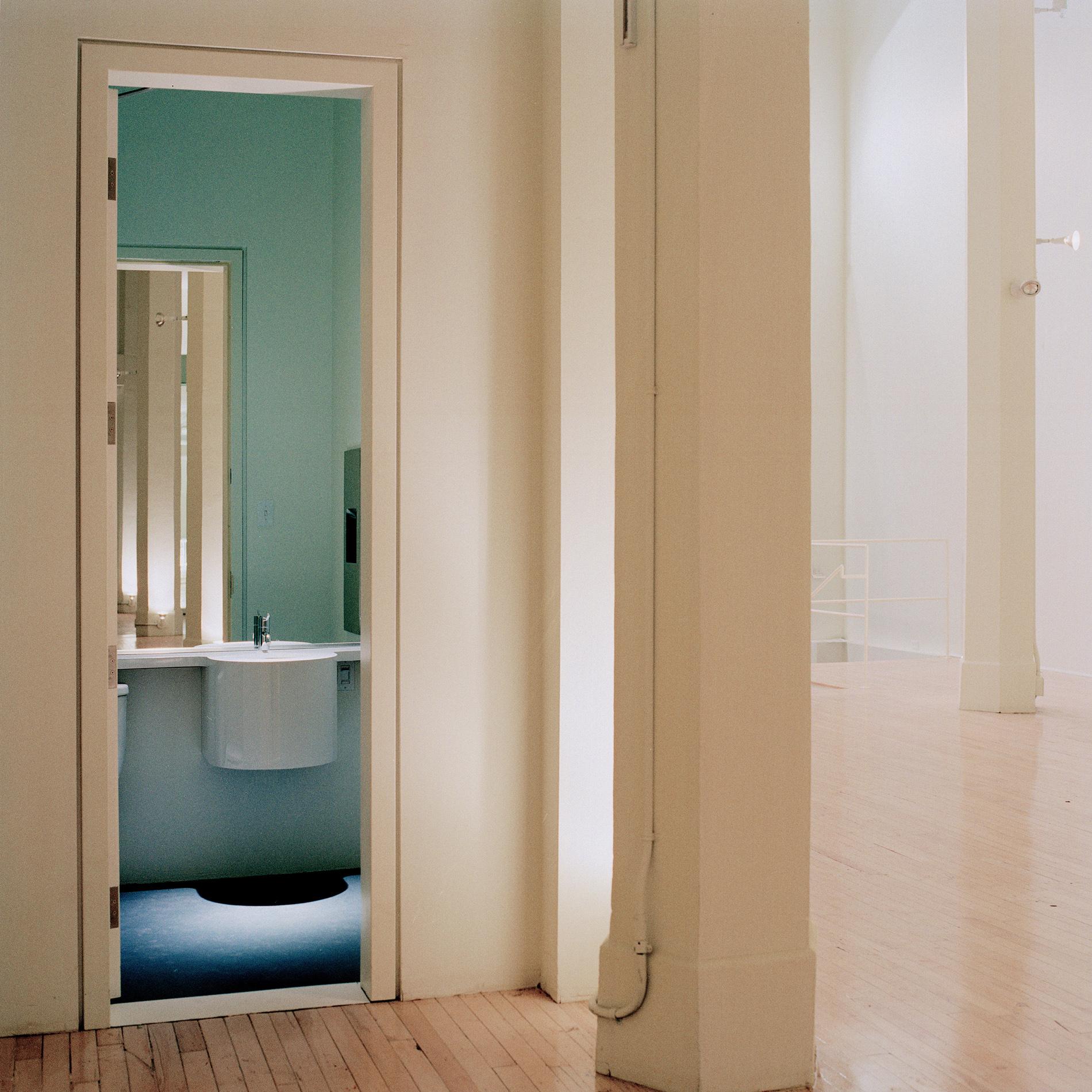 Porte d'accès à une toilette. L'étroitesse et la hauteur de la nouvelle porte renforcent le volume de l'espace central avec ses colonnes hexagonales de béton. Crédit photo © Marc Cramer.