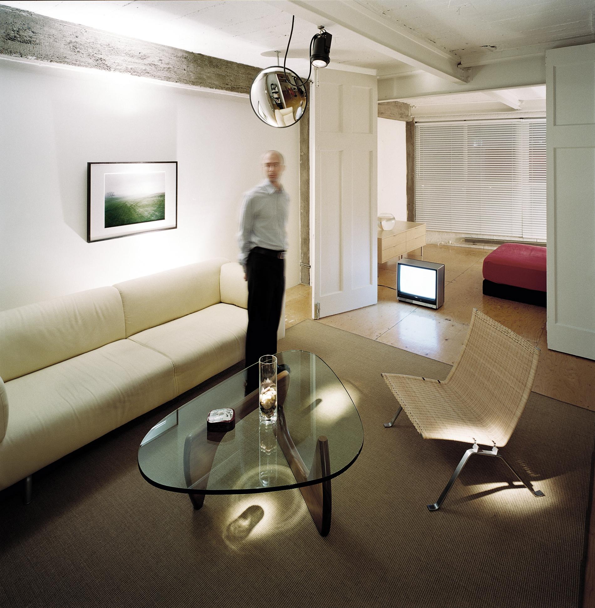Vue du salon avec table Noguchi et chaise PK22 de Poul Kjærholm. Des projecteurs d'éclairage PAR 36 au plafond créent des points lumineux sur le plancher. Crédit photo © Marc Cramer