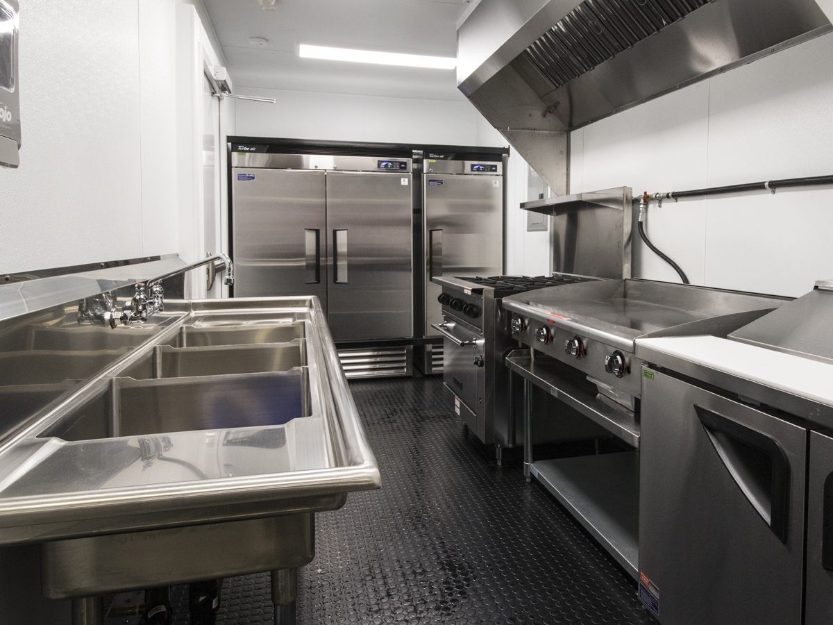 Containerized kitchen unit with range, flat top, cold wells, 3 compartment sink, cooler and freezer