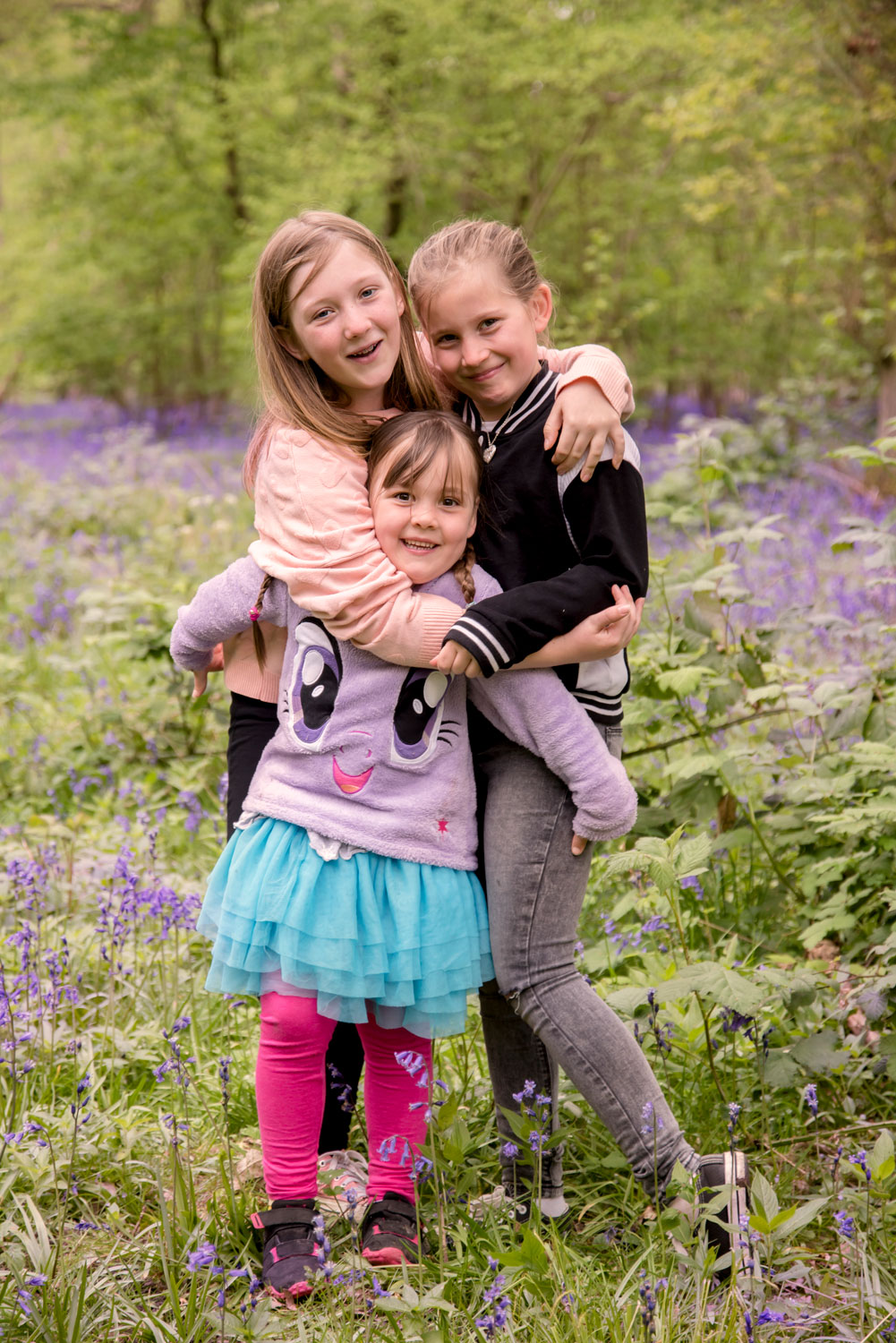 Family_photography_Ely_Cambridgeshire-3-girls-cuddling-in-the-bluebells.jpg