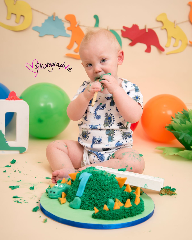 Cake_smash_photography_Ely_Cambridgeshire_first_birthday_dinosaur_themed_boy_eating_cake.jpg