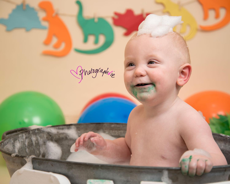 Cake_smash_photography_Ely_Cambridgeshire_first_birthday_dinosaur_themed_boy_in_tin_bath_with_bubbles_on_head.jpg