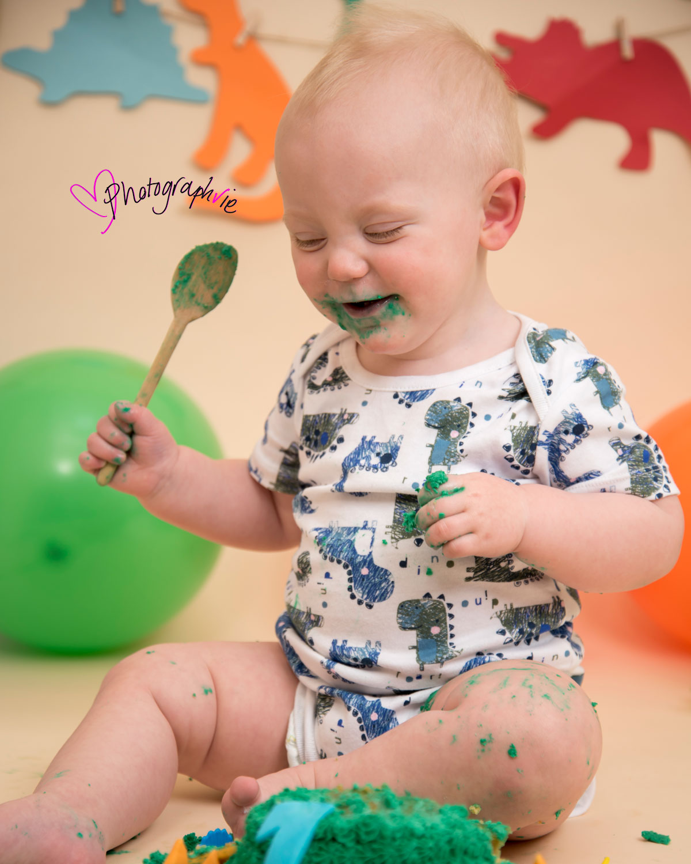 Cake_smash_photography_Ely_Cambridgeshire_first_birthday_dinosaur_themed_boy_looking_at_cake.jpg