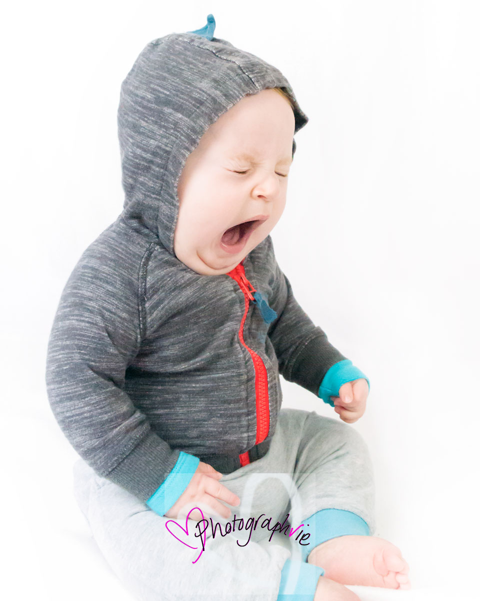 sleepy baby yawning through photoshoot sitter session in hoody white backdrop photographer in ely