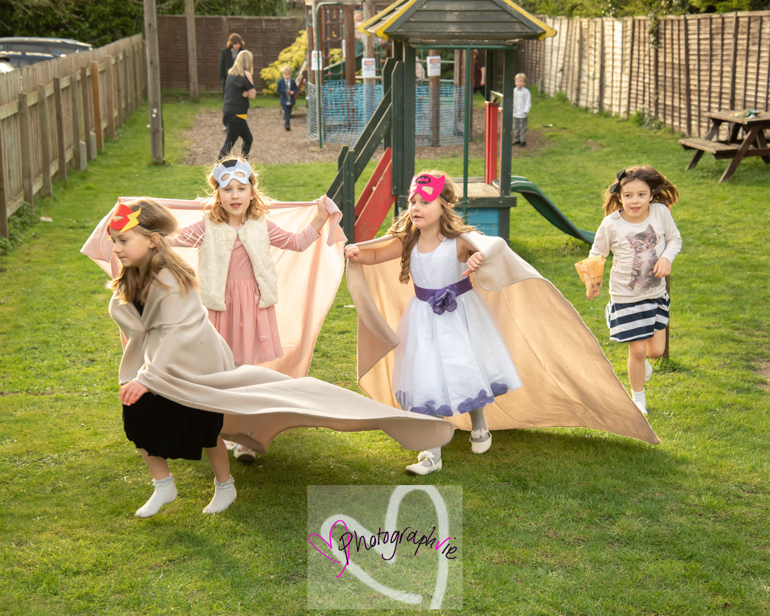 superhero masks on children playing at a wedding in soham, cambridge, wedding photography by vicki newman, relaxed fun photos