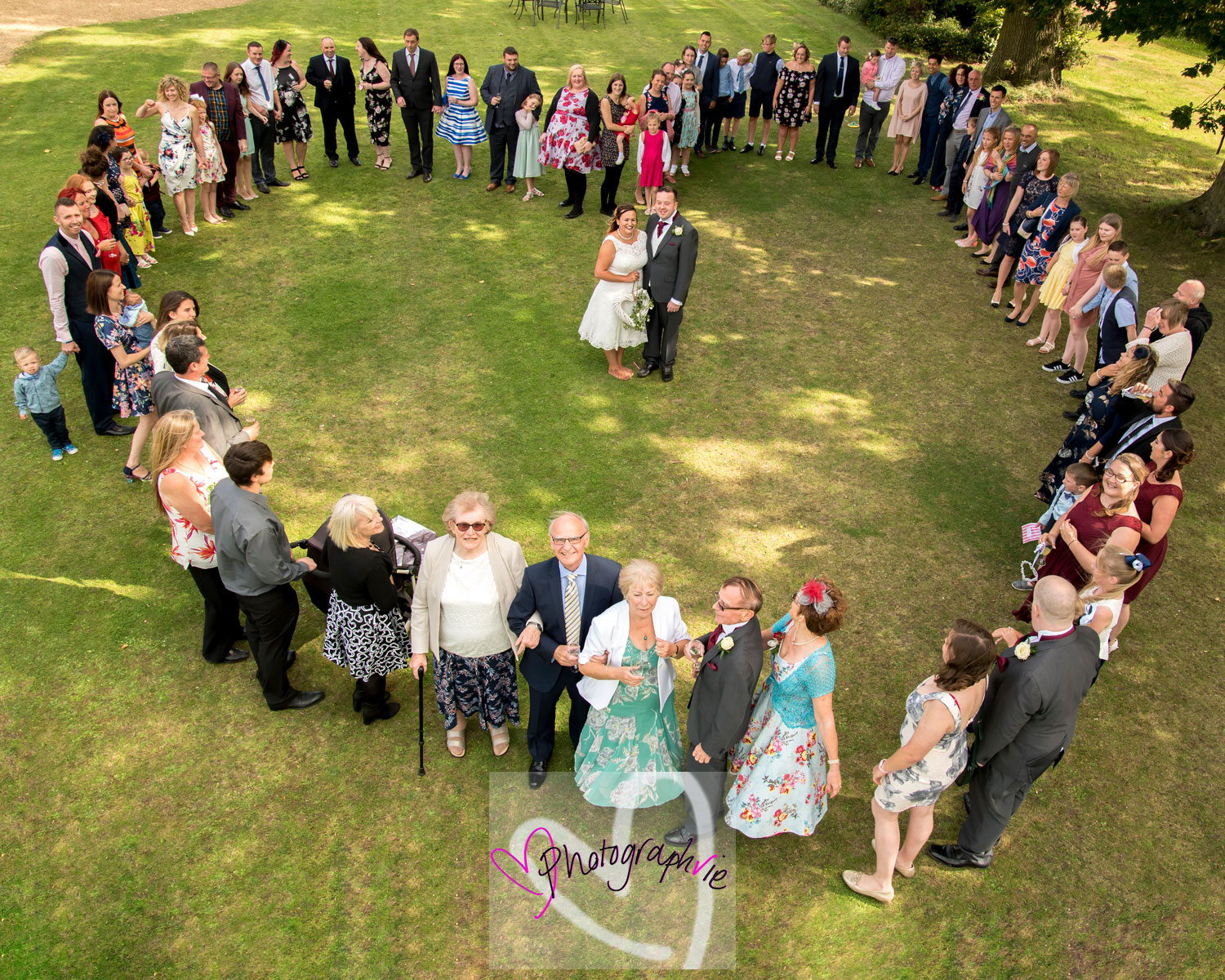 wedding photography in ely red barn norfolk wedding guests in a heart shape taken from a cherry picker on a tractor by wedding photographer vicki newman