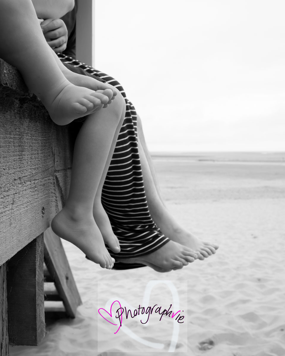 image of family photoshoot feet dangling from a beach hut at the seaside beach mini photoshoot norfolk