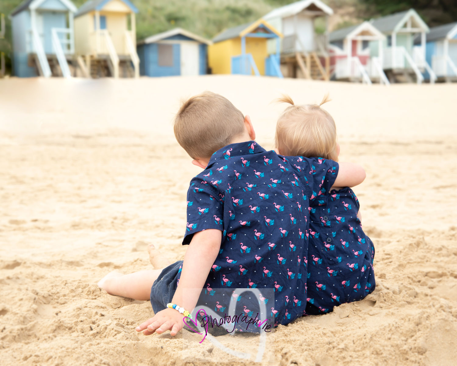 photo of siblings cuddling on the beach facing away from the camera family photoshoot in norfolk