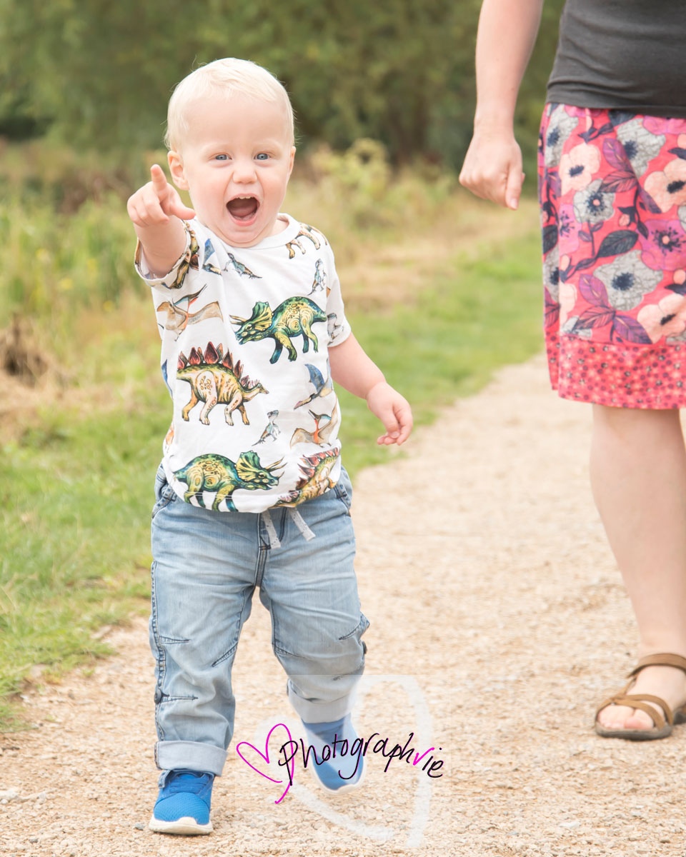 photo of toddler at summer mini photoshoot in ely pointing at the train with mum