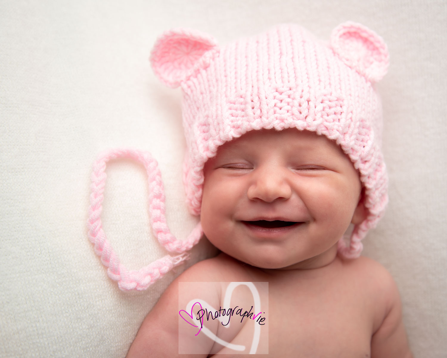 baby photoshoot newborn smiling in their sleep wearing pink hat baby smiles ely photoshoot