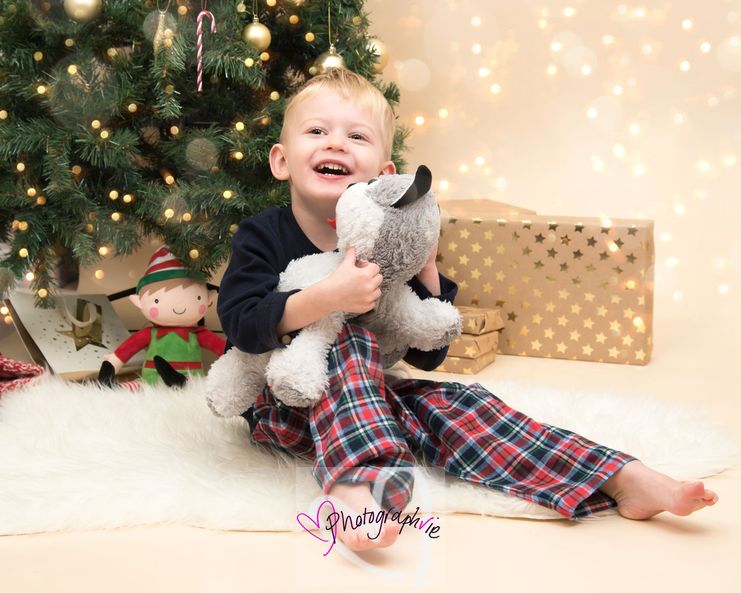 christmas photoshoot family child holding cuddly toy sentimental photo with christmas backdrop