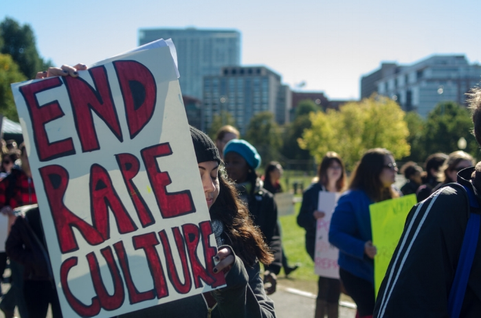 """A person at a demonstration holds a sign reading """"End rape culture."""" Source:   Chase Carter"""