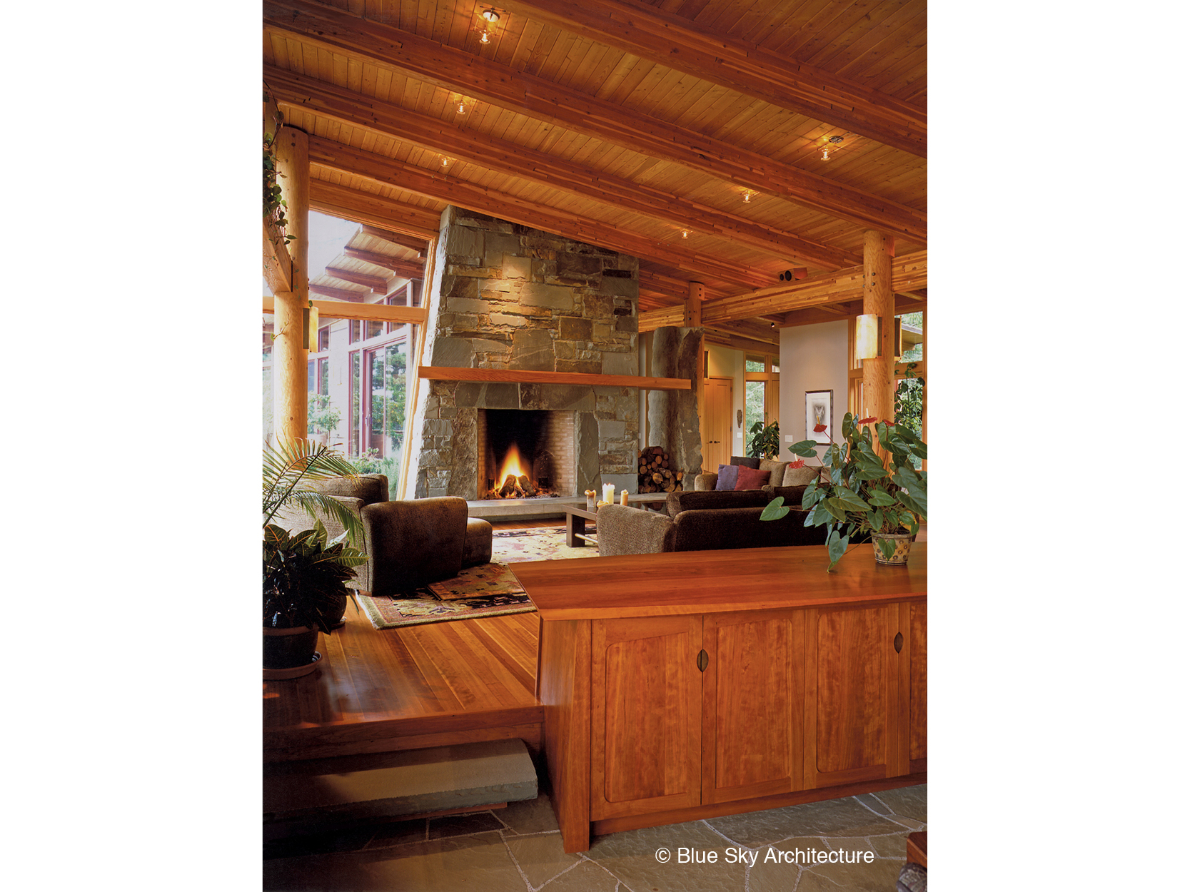 Sandstone slab fireplace with wood rafter ceiling in Hill House