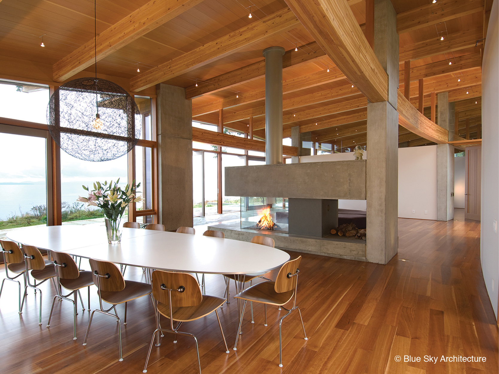 Dining room with concrete fireplace and wood rafters