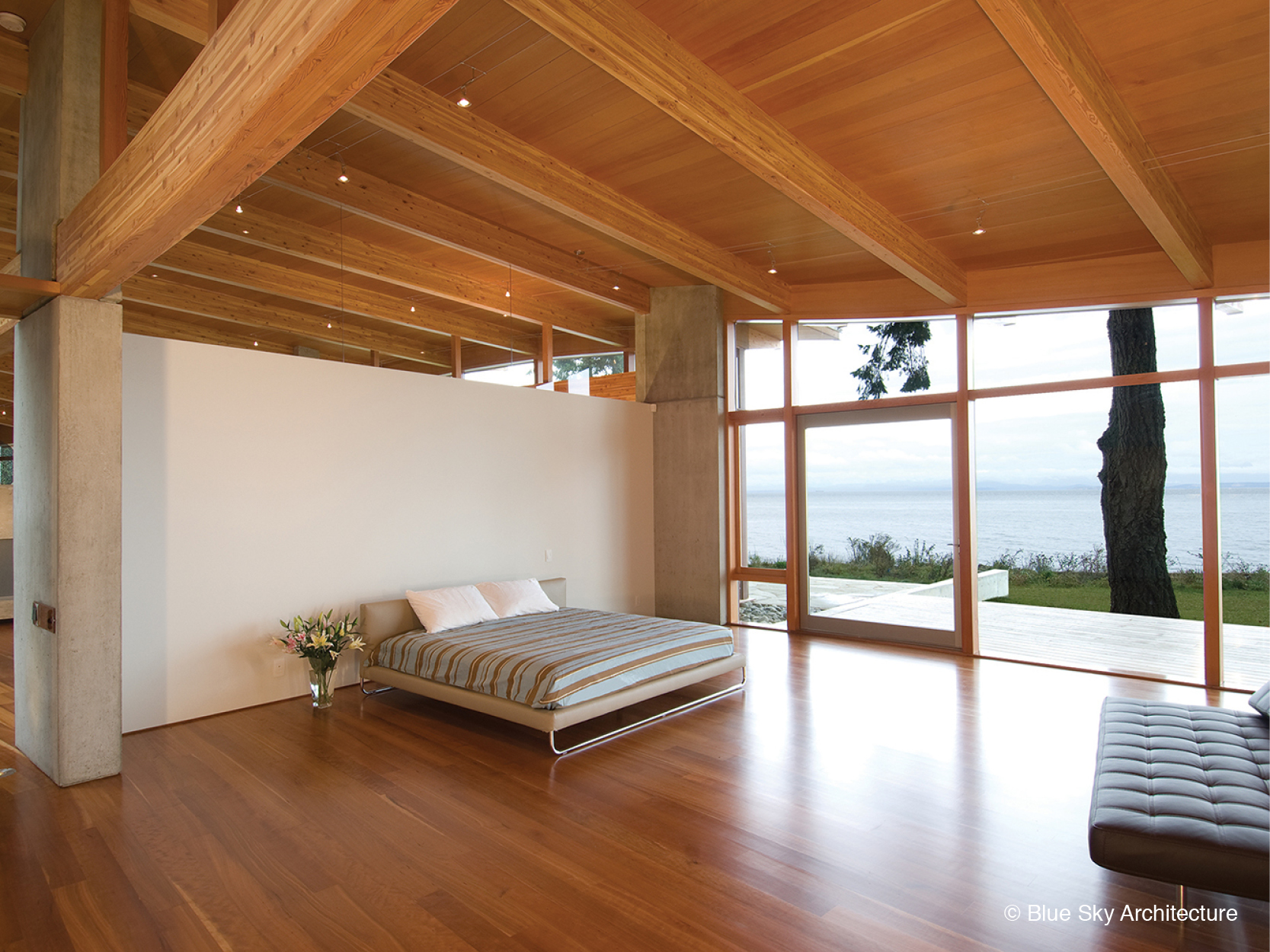Wood rafters and natural lighting in a minimalist bedroom