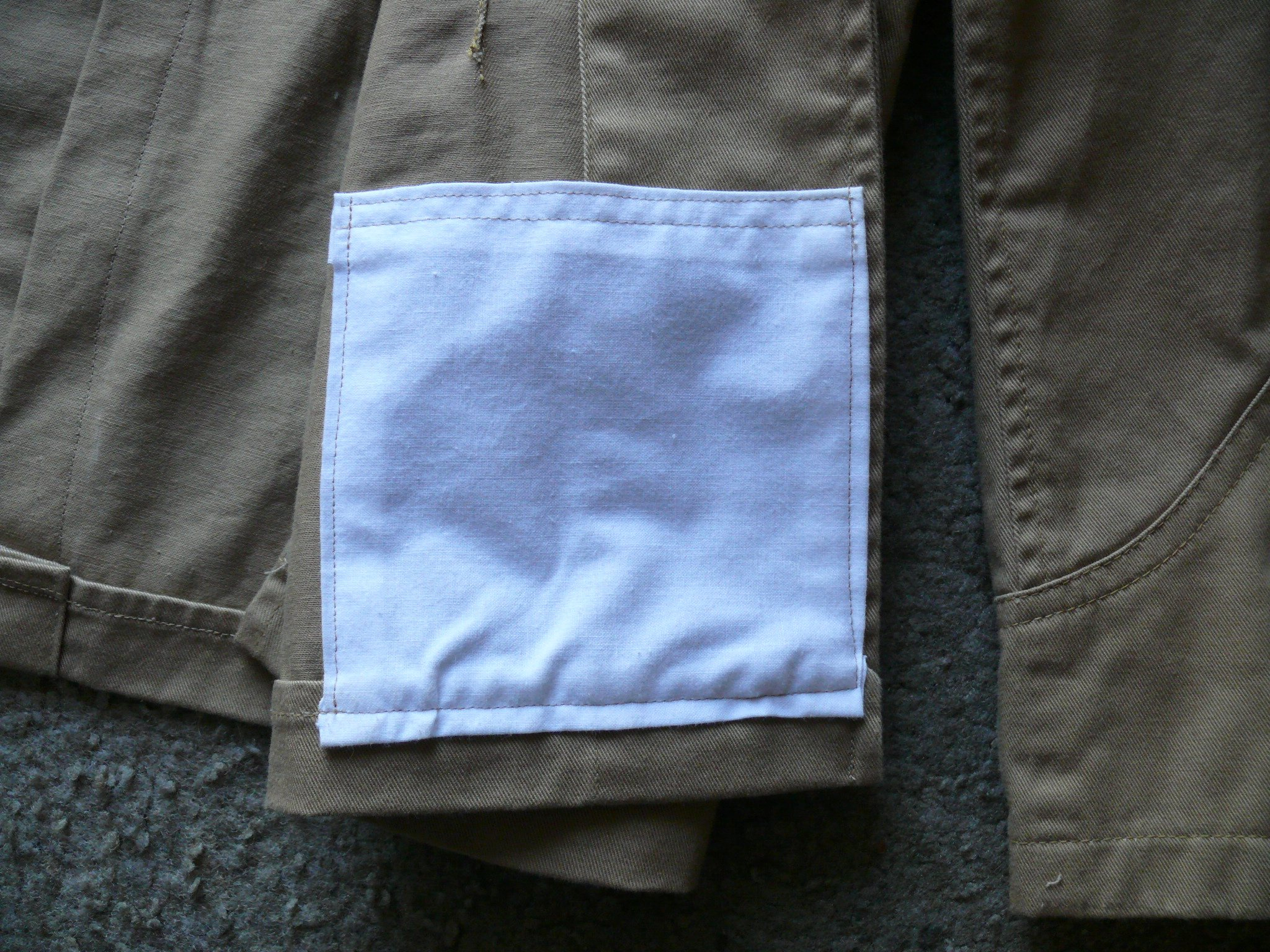 The new pocket topstitched into the inside of the tunic. The stitching of the pockets to the inside of the tunic shows through to the outside and that is correct. We see that in historic examples.