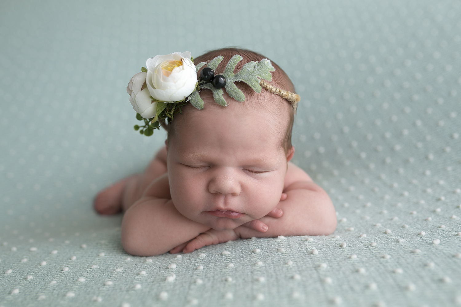 beautiful baby girl on tiffany blue with white flower crown with olive berries and pouty lips