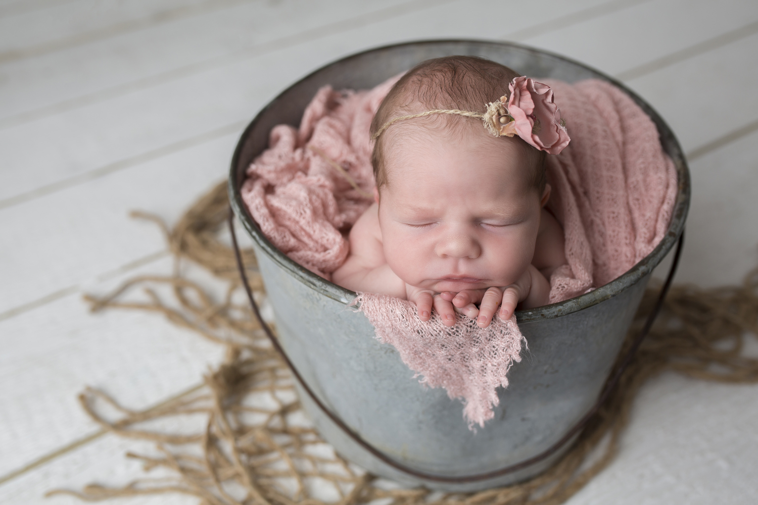 newborn baby girl in a rustic metal bucket posed perfectly surrounded by pink