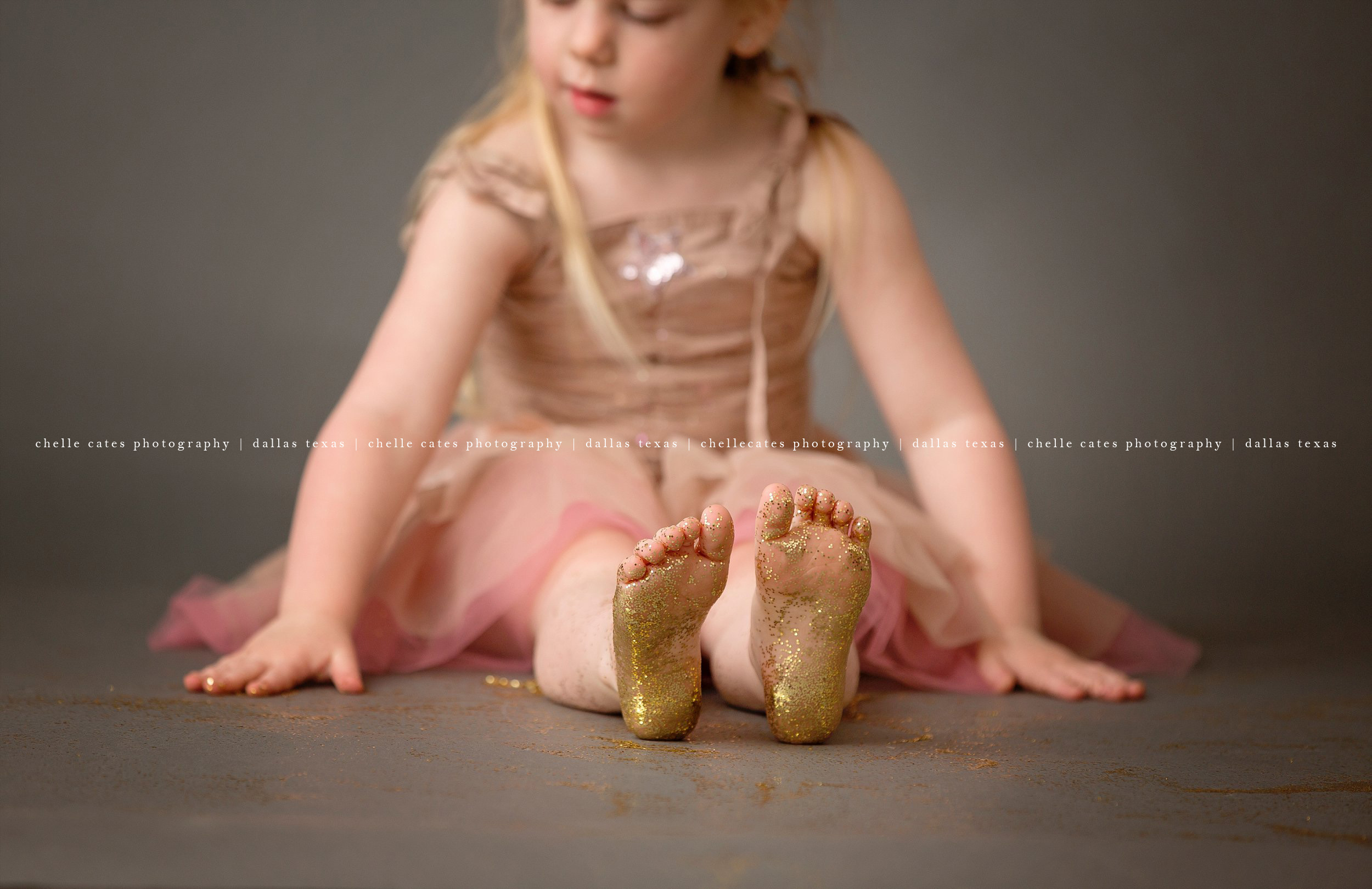 blonde four year old in low pigtails sitting on dark gray backdrop in her pink tutu dress playing in gold glitter. gold glitter all over her feet and toes at the studio in dallas texas