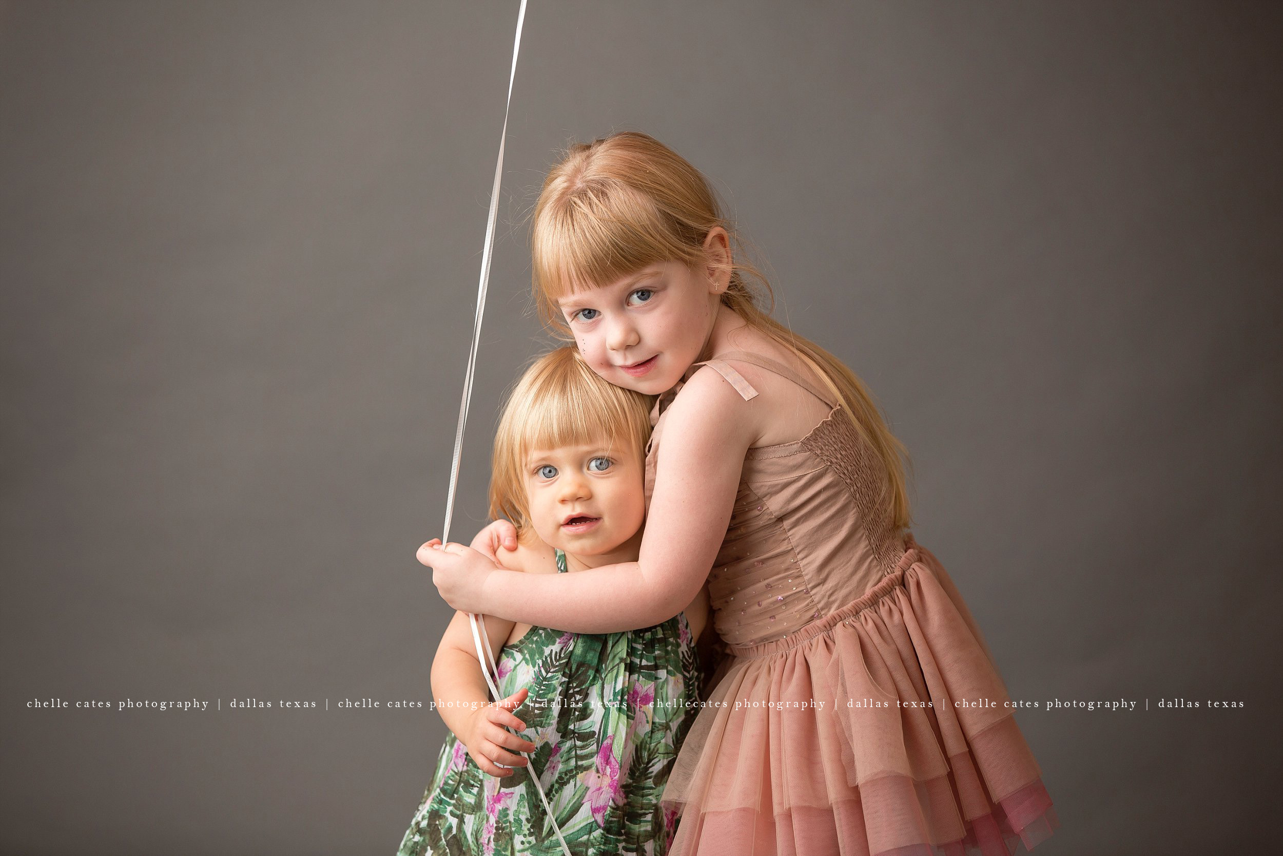 Portrait of two girls who are sisters. Photographed at Chelle Cates Photography Studio in Dallas Texas.