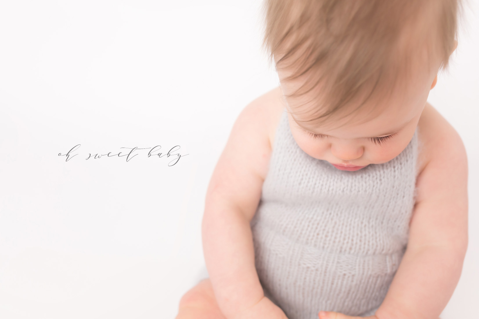 6 month old little baby boy sitting on white background in a pale blue knitted romper. He has light brown hair with a perfect part and endless eyelashes. He is looking down at his hands and a wooden toy.