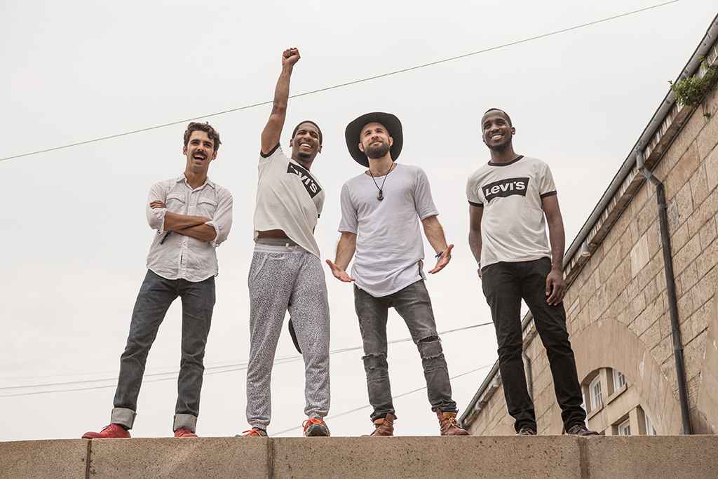 Jon Batiste & Stay Human pose for a photo on top of a wall inside Fort Adam. From left, are: Eddie Barbash, Jon Batiste, Joe Saylor and Ibanda Ruhumbika.