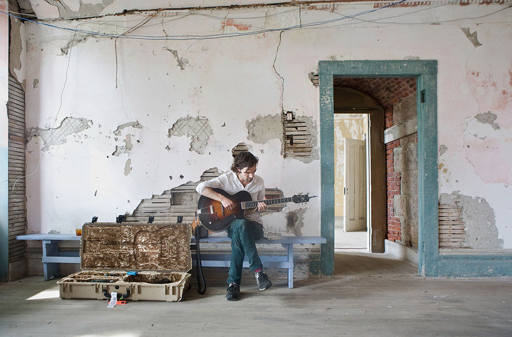 Brad Barr of The Barr Brothers plays guitar during a quiet moment inside Fort Adams.