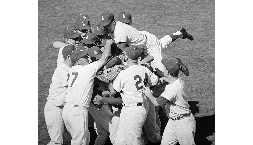 Dodgers win the World Series  Teammates all but bury Sandy Koufax after he pitched them to a 2-1 victory, completing the Dodgers' sweep of the Yankees for the World Series championship.