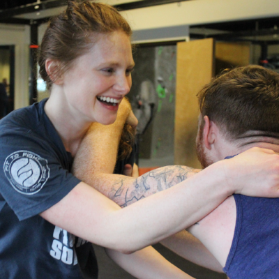 """Kathryn Angstadt  is the Chief of Staff at N-Flux. Kathryn is a Fit To Fight certified instructor and a green belt. Kathryn believes in """"the offensive mindset"""" —cultivating mental and physical resiliency by identifying personal limits and pushing past them in every training. She is interested in tactical shooting and Obstacle Course Racing."""