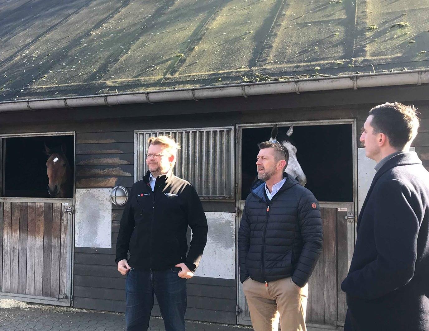 Direktør på Klampenborg Galopbane, Carsten Baagøe Schou (tv) viser Peter Brüchmann og Jonas Hebo Rasmussen rundt i staldene.