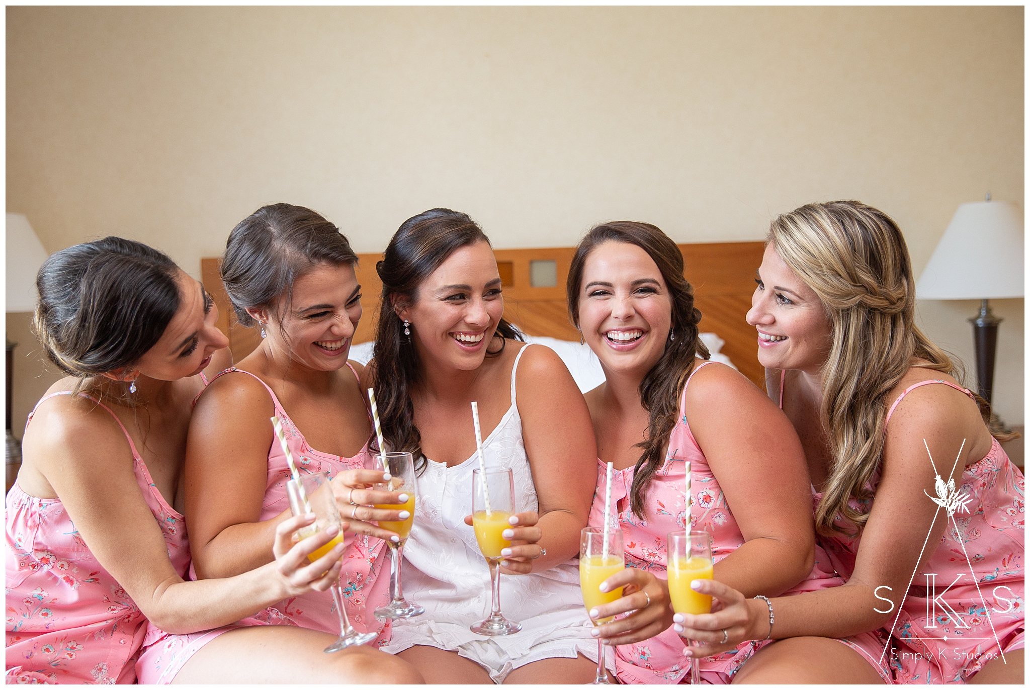 Bridesmaids wearing pink pajamas and drinking mimosas