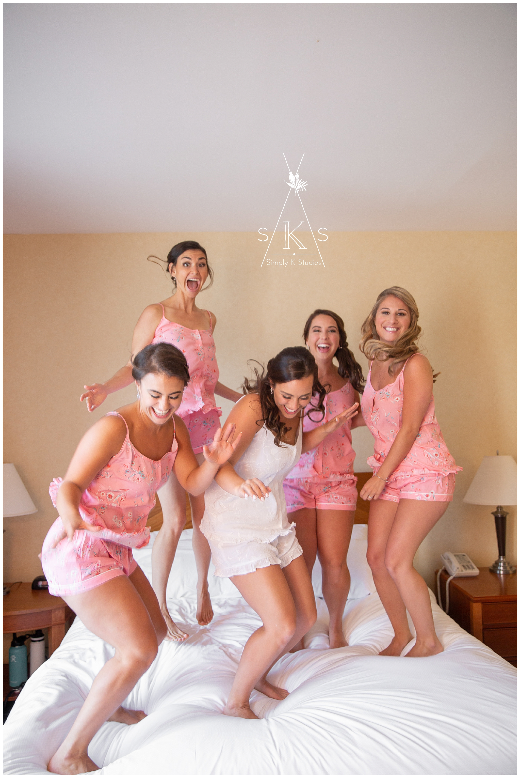 Bridesmaids jumping on a bed