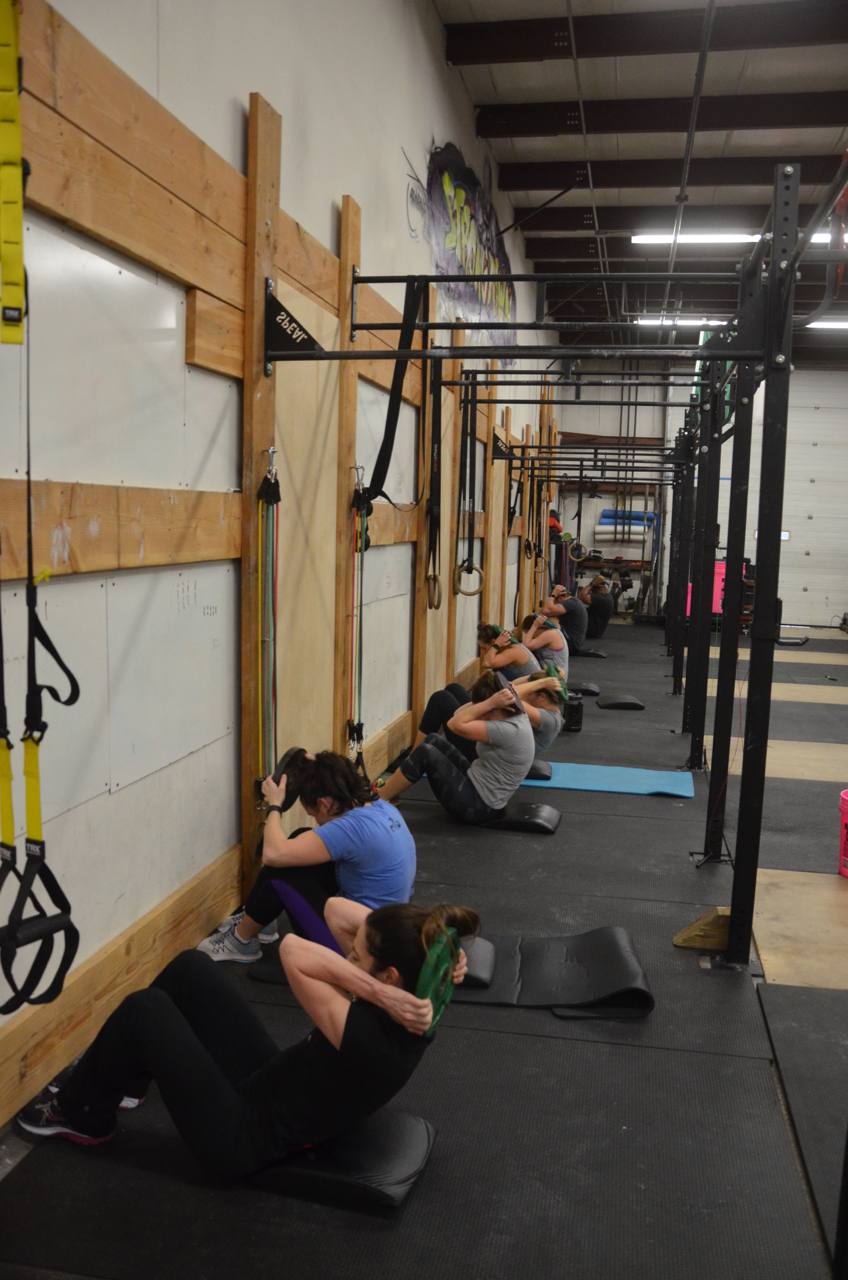 Holly and the 9:30 class working through their 50 weighted sit-ups.