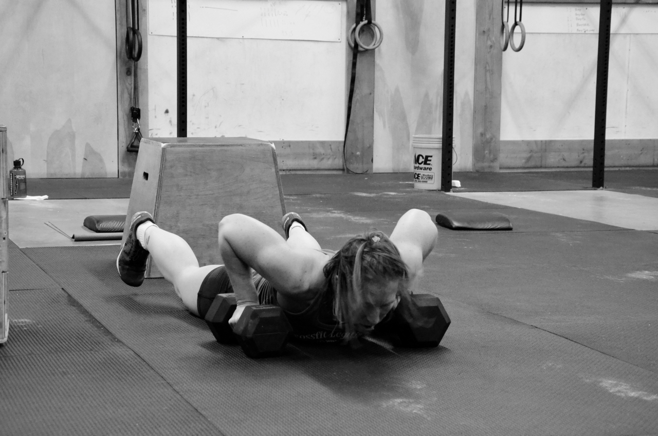 Rachel making shire to go chest to deck on her Dumbbell Burpee Deadlifts.