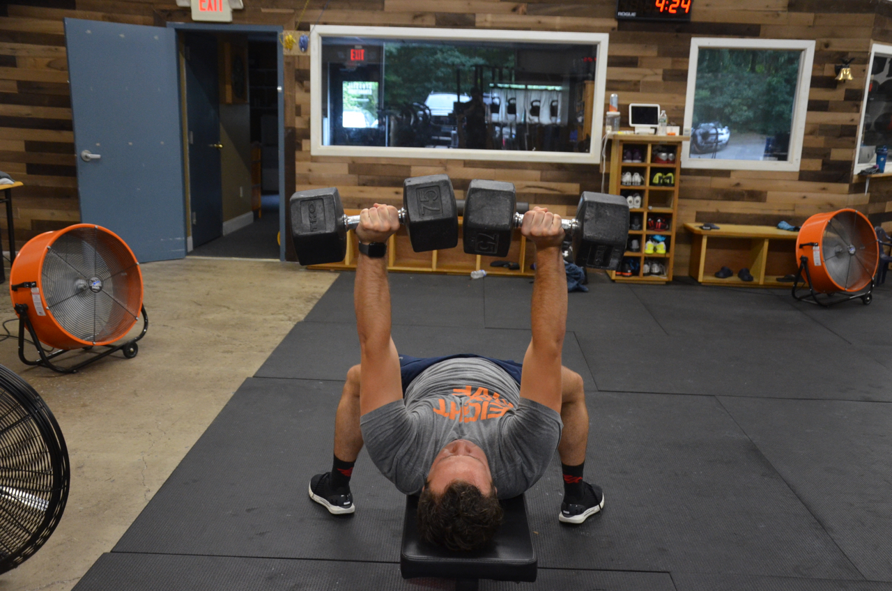 Dan F. showing a strong lockout on his dumbbell bench press.