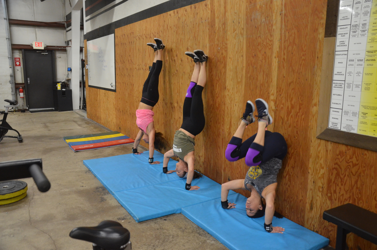 Jen, Kelly and Angela making their handstand push-ups look easy.