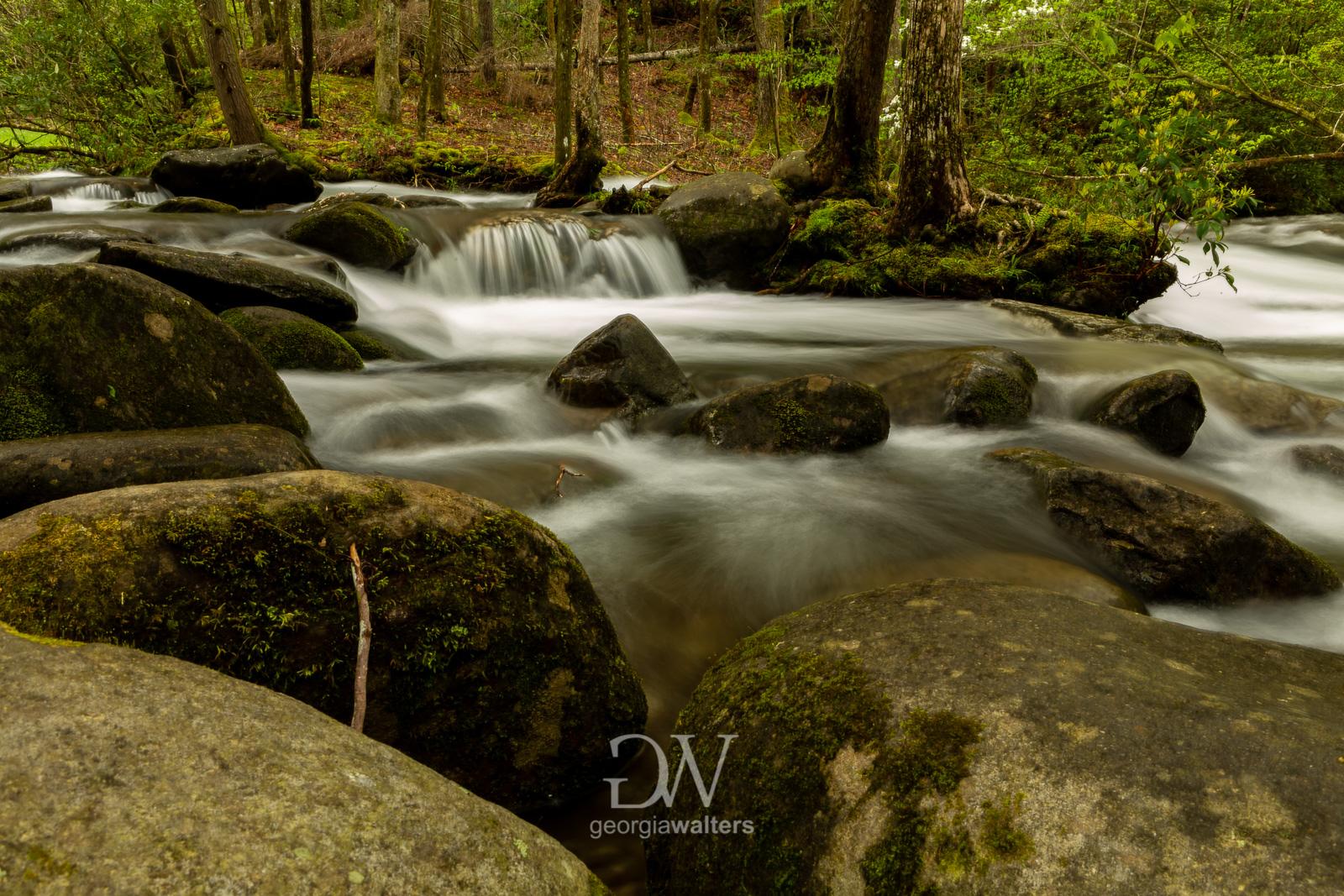 Misty water flows around a rocks in a creek.