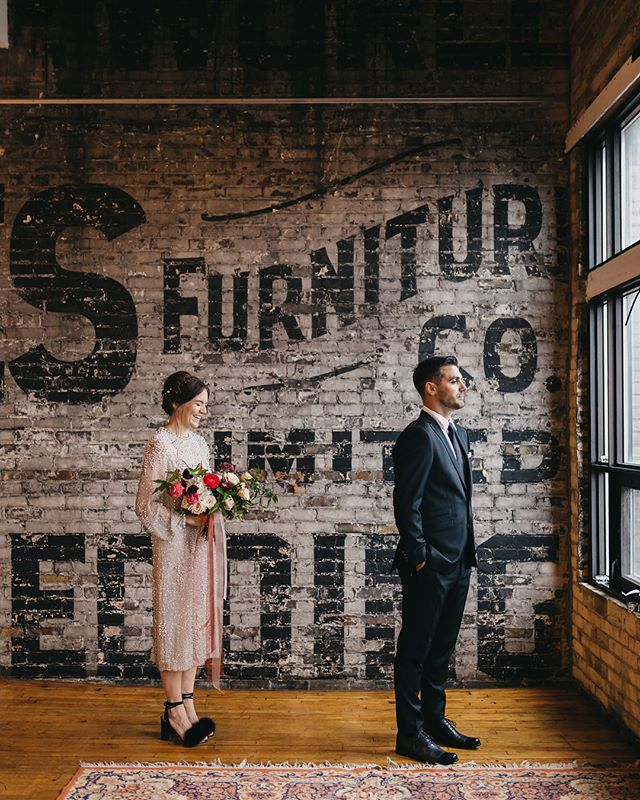 """Lesley + Matt ✨ Swipe through for their """"first look"""" • Featured on @junebugweddings """"A vintage shift midi dress, black feather heels, and a braided hair crown make Lesley's alternative bridal style one of our all-time faves! Lesley and Matt's wedding at Toronto venue The Burroughes @theburroughes combined the couple's tendencies to enjoy sophisticated vintage-inspired details with all the coolness of an industrial venue. We love how Lesley and Matt made their ceremony special with warm details like candles, Persian rugs, loose florals lining the aisle, and a very personal song list. Kayla Rocca Photography captured every ounce of coolness..."""" make up by @samcomptonmakeup • hair by @justinrousseau • planning by @lexingtonandco"""