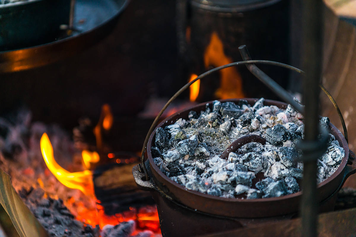 Placing-the-coals-next-to-the-camp-oven.jpg