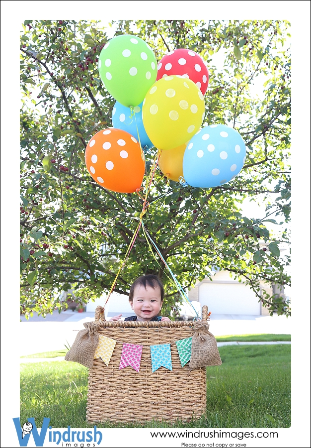 7 month old baby boy photographed outside in Calgary Alberta in basket with balloons in hot air balloon themed baby photo shoot photographed by Suzie Broadbent of Windrush Images