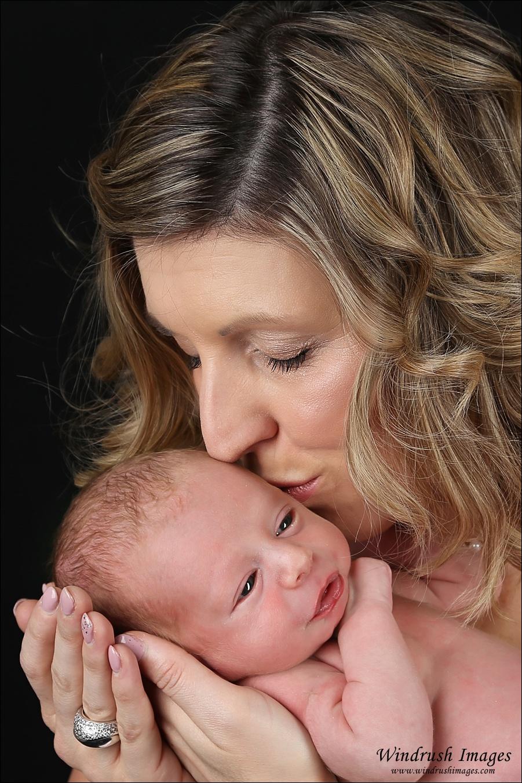 Mom kissing awake baby at Newborn photo shoot in Calgary