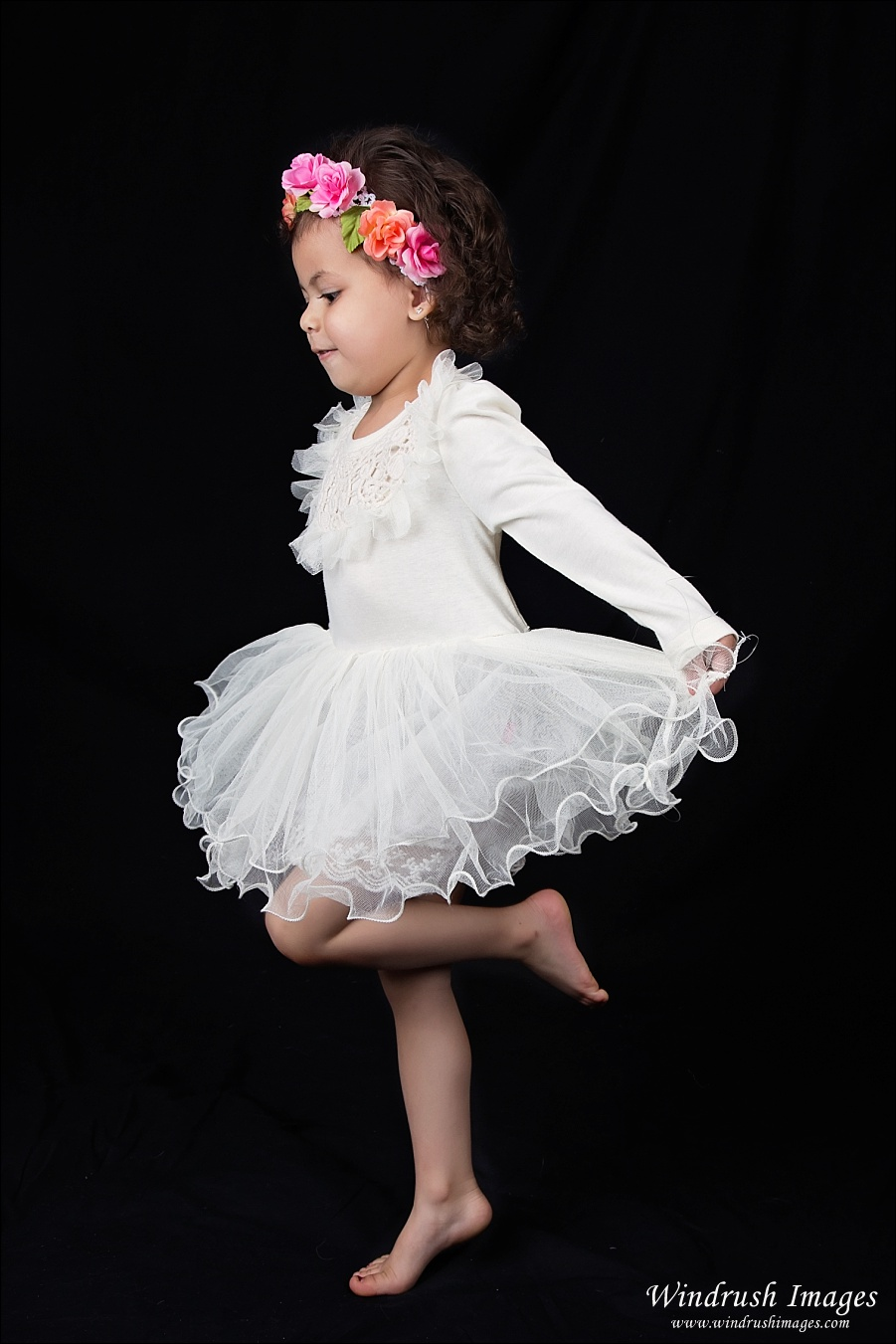 Calgary kids photographer of girl dancing joyfully wearing white dress and floral headband