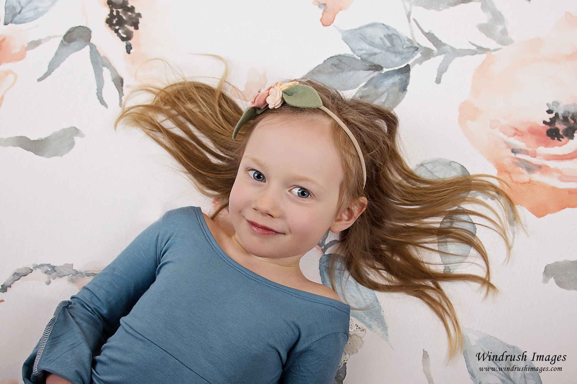 Beautiful girl with hair spread out resting on peach floral background for spring photos in Calgary