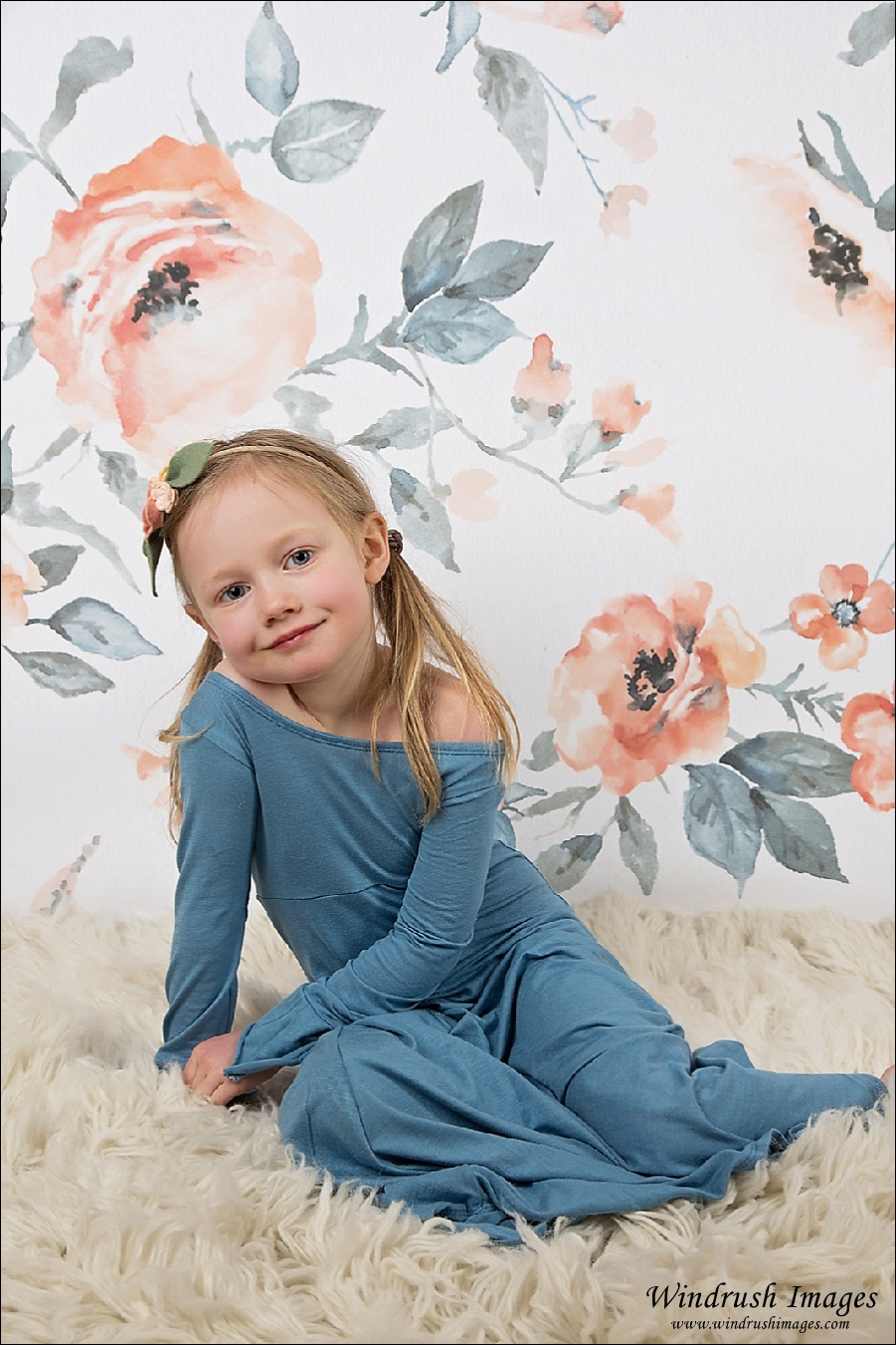 Calgary spring kids photo of little girl in blue dress sitting in front of peach flower background in srudio
