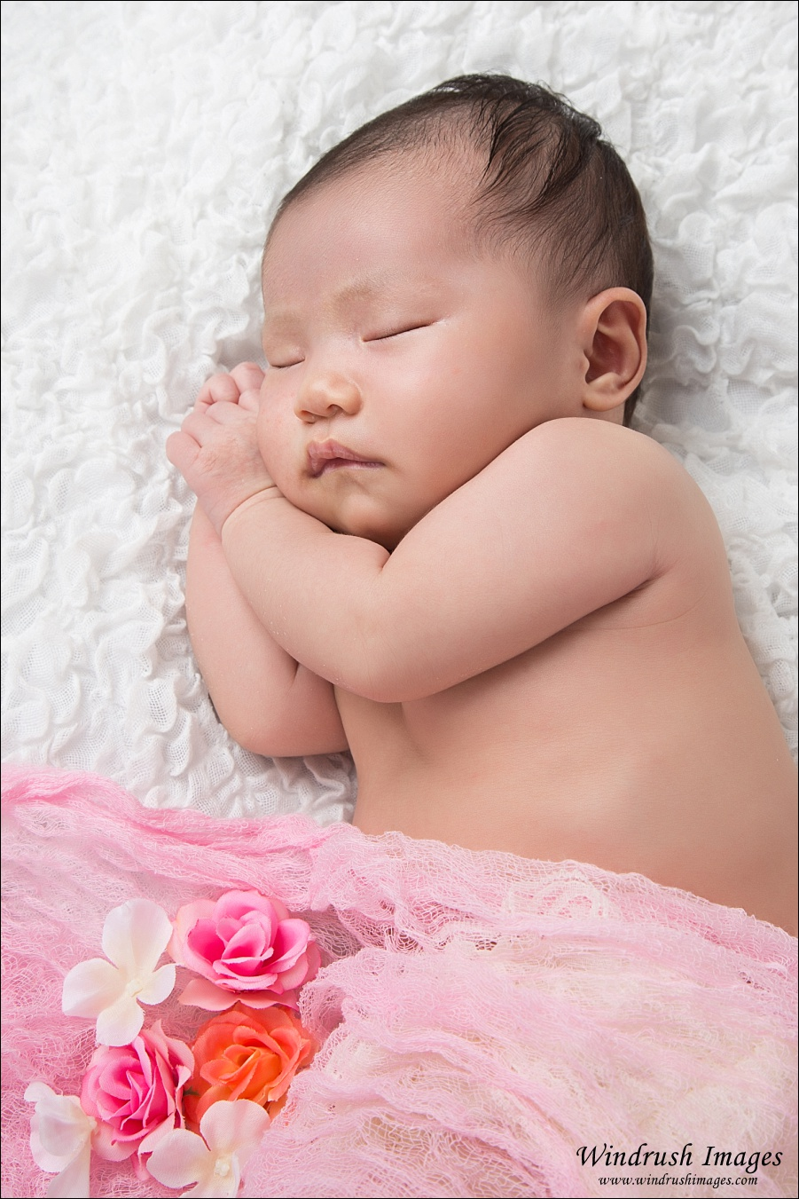 One month old baby sleeping with pink flowers Calgary newborn photography