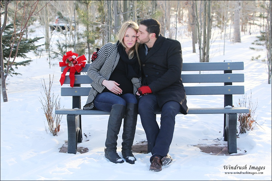 Winter maternity photography of beautiful couple kissing on a bench in the snow in Botanical Gardens of Silver Springs in Calgary